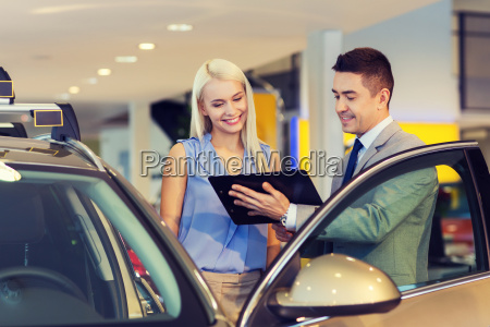 happy woman with car dealer in