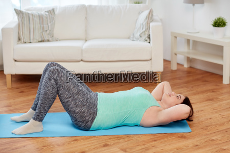 plus size woman exercising on mat