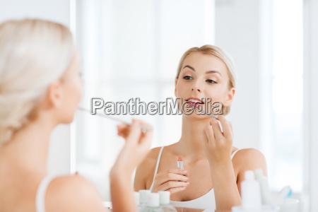 woman with lipstick applying make up