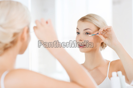 woman fixing makeup with cotton swab