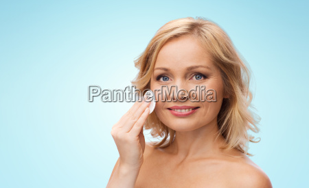 happy woman cleaning face with cotton