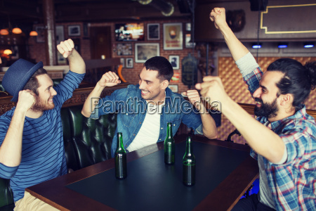 happy male friends drinking beer at