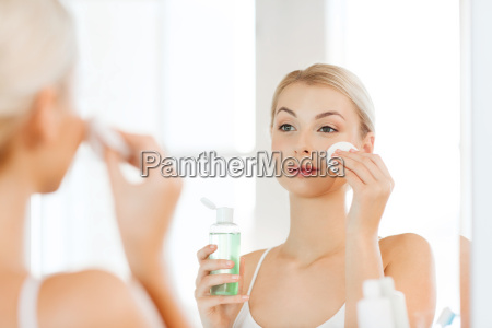 young woman with lotion washing face