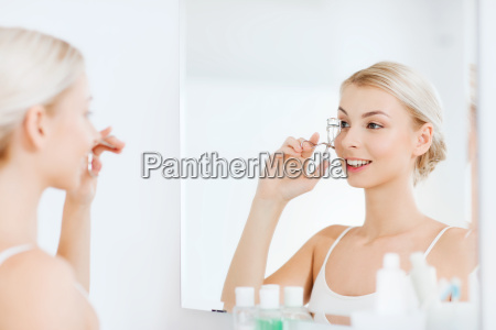 woman with curler curling eyelashes at
