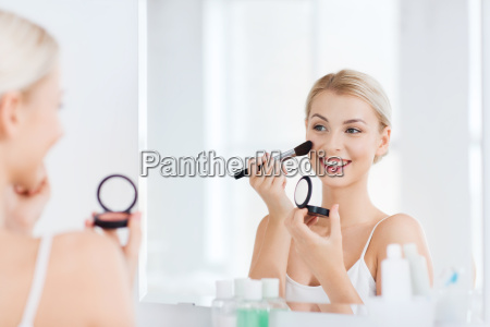 woman with makeup brush and blush