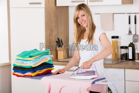 smiling woman ironing clothes with electric