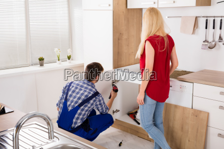 male worker repairing drawer in kitchen