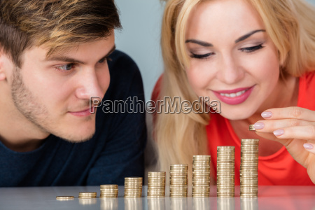 couple sitting with stacks of coins
