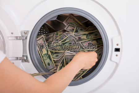 person inserting money in washing machine