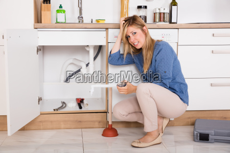 frustrated woman having kitchen sink problem