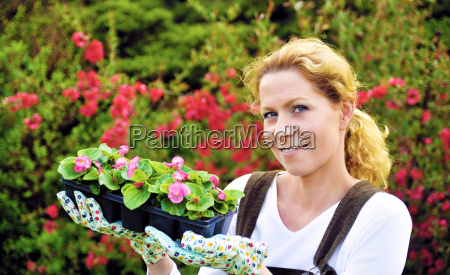 young woman gardening holding young flower