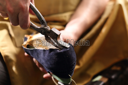the shoemaker manually handles shoes in
