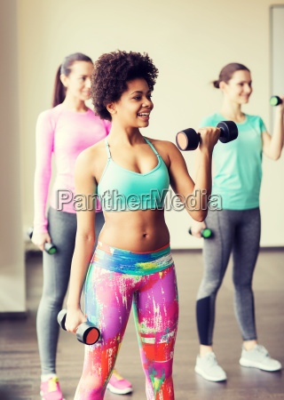 group of happy women with dumbbells