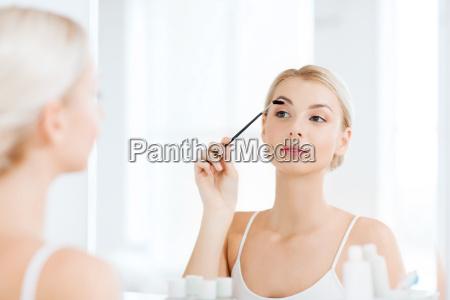 woman brushing eyebrow with brush at