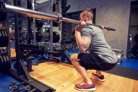 young man flexing muscles with bar