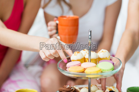 friends or teen girls eating sweets
