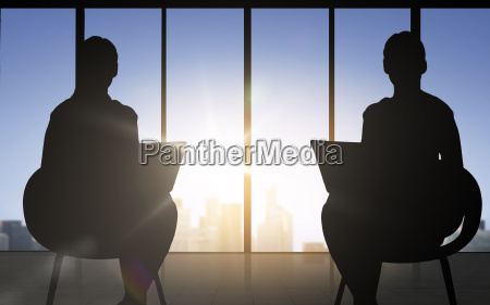 silhouette of two business women with