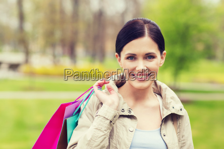 smiling woman with shopping bags coming
