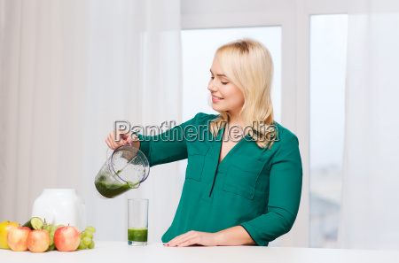 happy woman with blender jug pouring