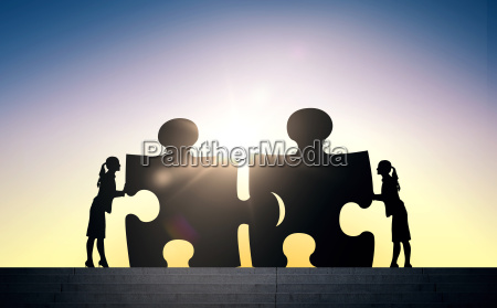 silhouette of two business women connecting