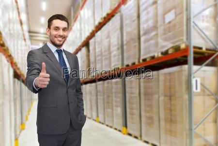happy man at warehouse showing thumbs