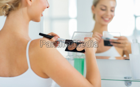 woman with makeup brush and foundation