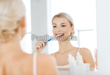 woman with toothbrush cleaning teeth at
