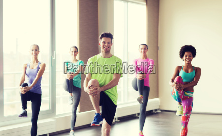 group of smiling people exercising in