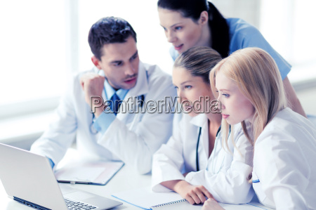 group of doctors looking at tablet