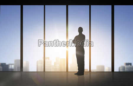 silhouette of business man over office