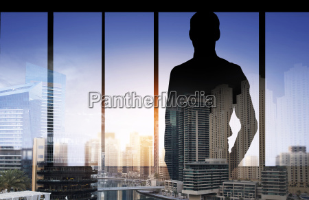 silhouette of business man over city