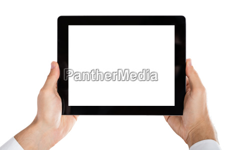 mans hand holding digital tablet