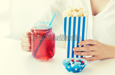 woman with popcorn and drink in