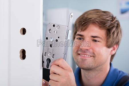 mans hand installing door lock in