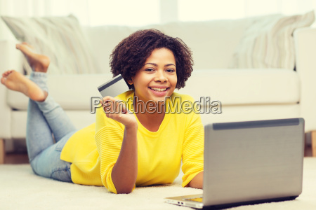 happy african woman with laptop and