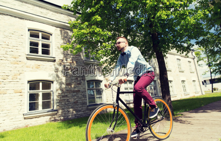 happy young hipster man riding fixed
