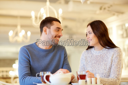 happy couple drinking tea at cafe