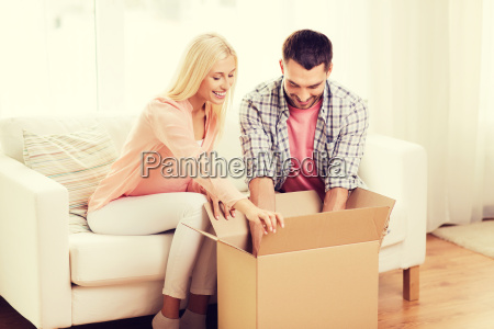 happy couple with cardboard box or
