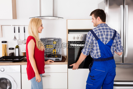 male worker installing oven for repairing