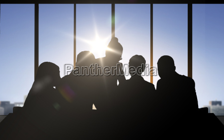 business people silhouettes over office background