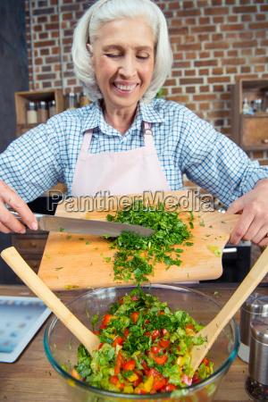 woman cutting salad greens