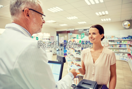 woman giving money to pharmacist at