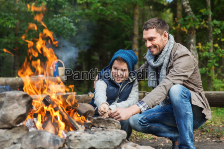 father and son roasting marshmallow over