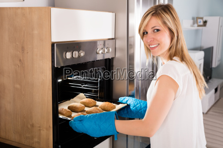 woman taking baking tray out from