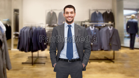 happy young businessman over clothing store
