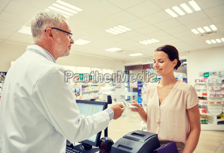 woman, giving, money, to, pharmacist, at - 20059494