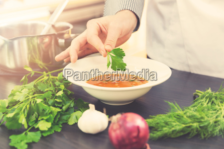 chef decorating soup with herbs in