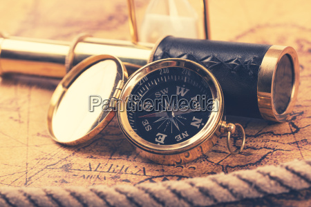 vintage compass and telescope on ancient