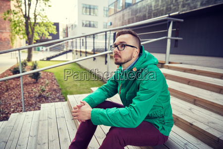 happy young hipster man sitting on