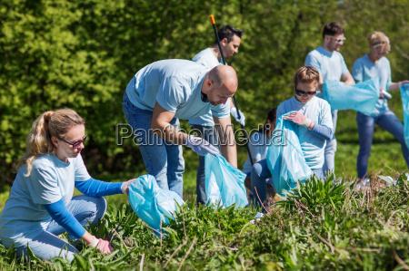 volunteers with garbage bags cleaning park